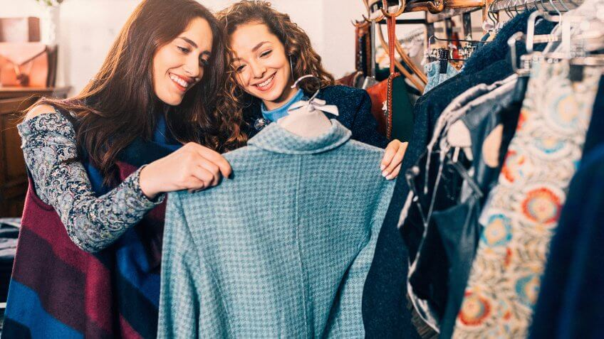 Two friends shopping for clothes in a store.