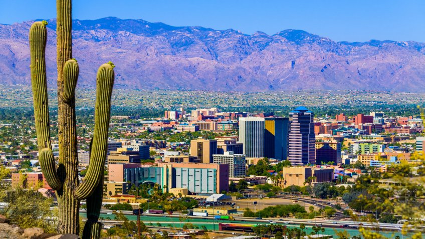 Tucson Arizona skyline cityscape framed by saguaro cactus and mountains.