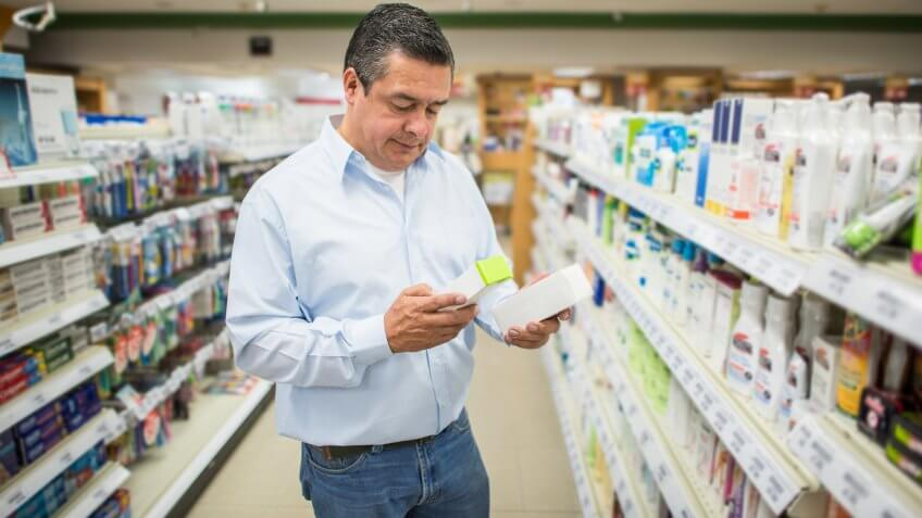Man shopping at the pharmacy and comparing two medical products - healthcare and medicine concepts.