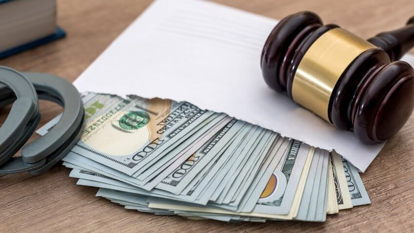 Biggest Money Scams of All Time, Handcuffs, corruption. dollars in an envelope, gavel and book judge.