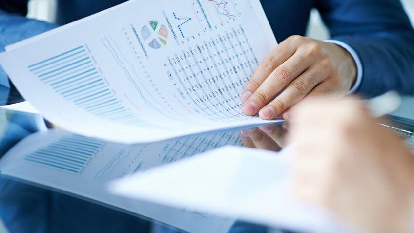 Hands of businessman examining financial report.
