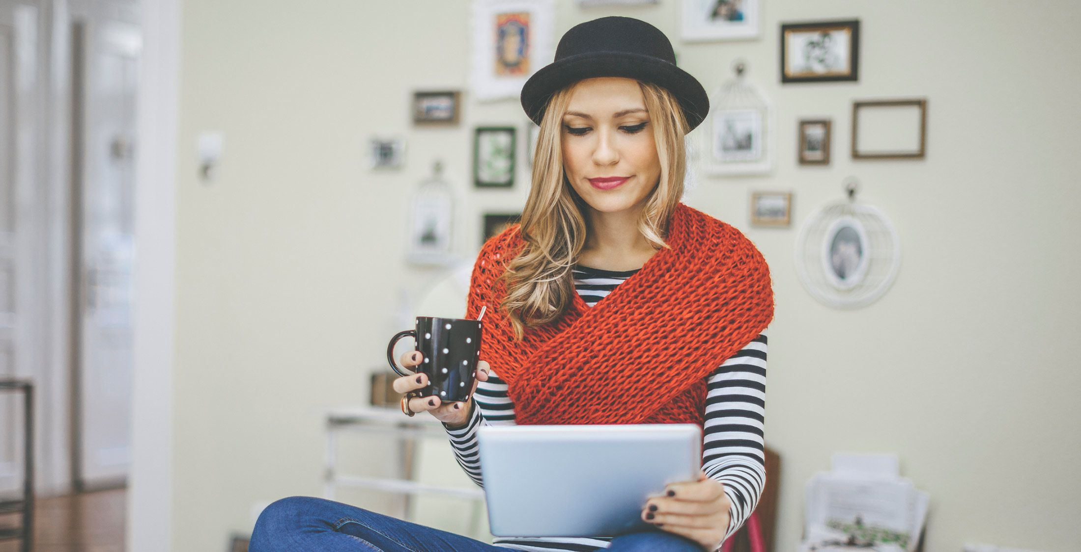 girl looking at tablet drinking coffee