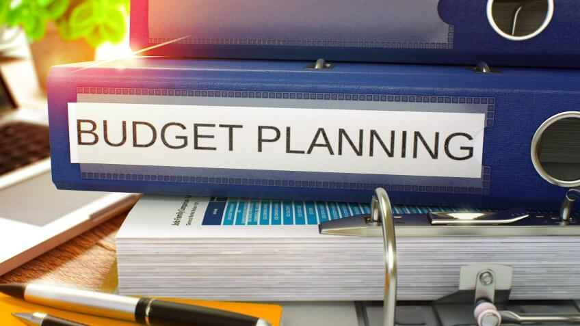 Blue Ring Binder with Inscription Budget Planning on Background of Working Table with Office Supplies and Laptop.