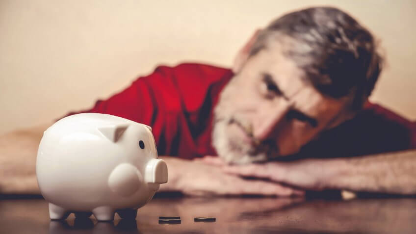 Senior man looking at piggy bank.