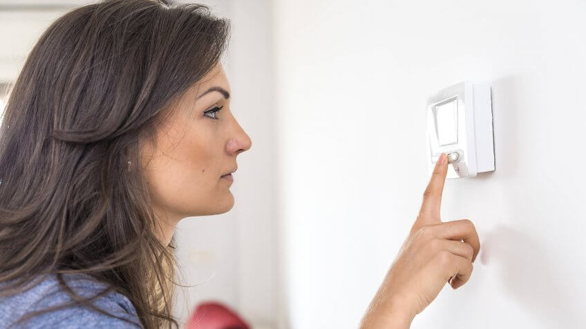 Beautiful woman push button digital thermostat at house.