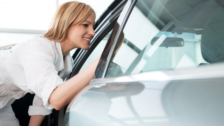 Mid adult woman looking through a opened window of a car in a showroom.
