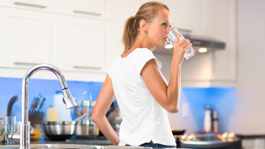 Pretty, young woman in her modern, clean and bright kitchen, pouring herself and drinking a glass of cold tap water(color toned imagey; shallow DOF).