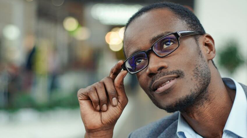 Portrait of handsome afro american man wearing grey suit and glasses.