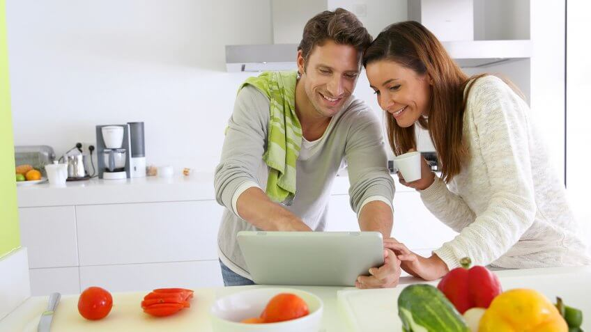 Couple in home kitchen looking for lunch recipe.