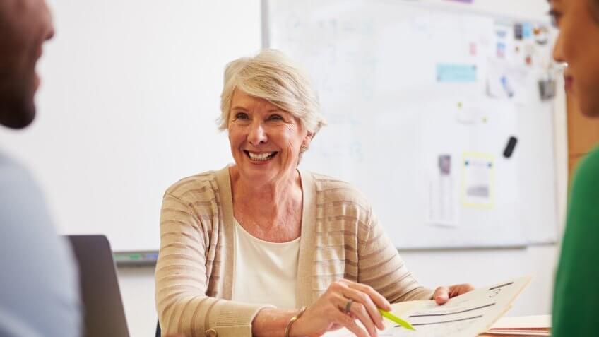 Senior teacher at desk talking to adult education students.