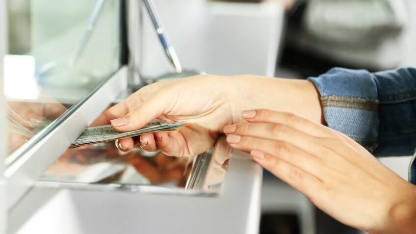 woman giving her money to someone behind a teller window