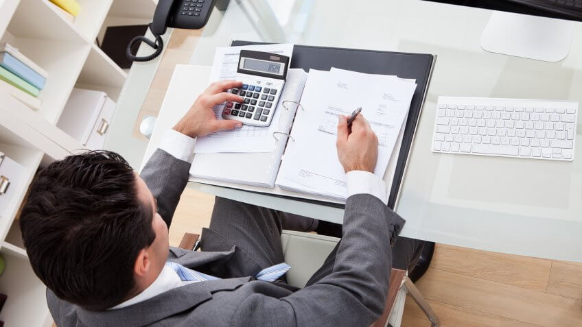 11902, Horizontal, man working on financial documents