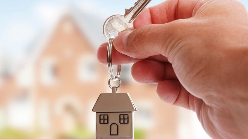 Holding house keys on house shaped keychain in front of a new home.