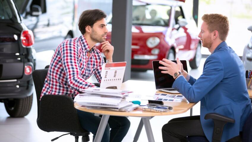 car agent talking with male customer at car dealership saloon.