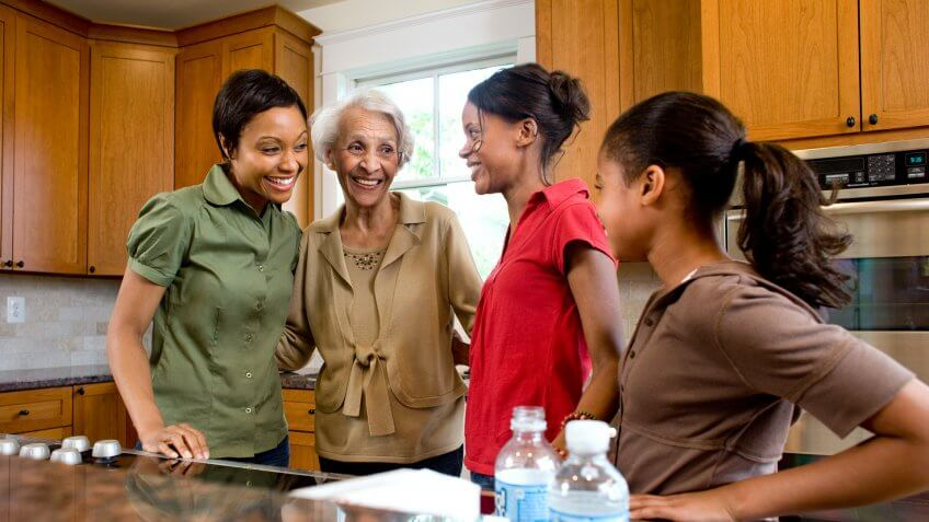 Multigenerational family talking in kitchen.