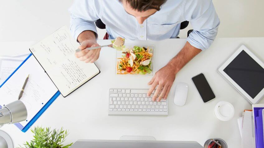 Overhead View Of Businessman Working At Computer In Office Eating Lunch.