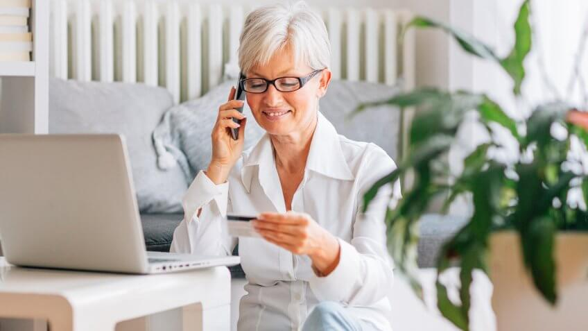Happy Mature woman sitting on floor in her living room and using laptop for online banking, online shopping or just fun.
