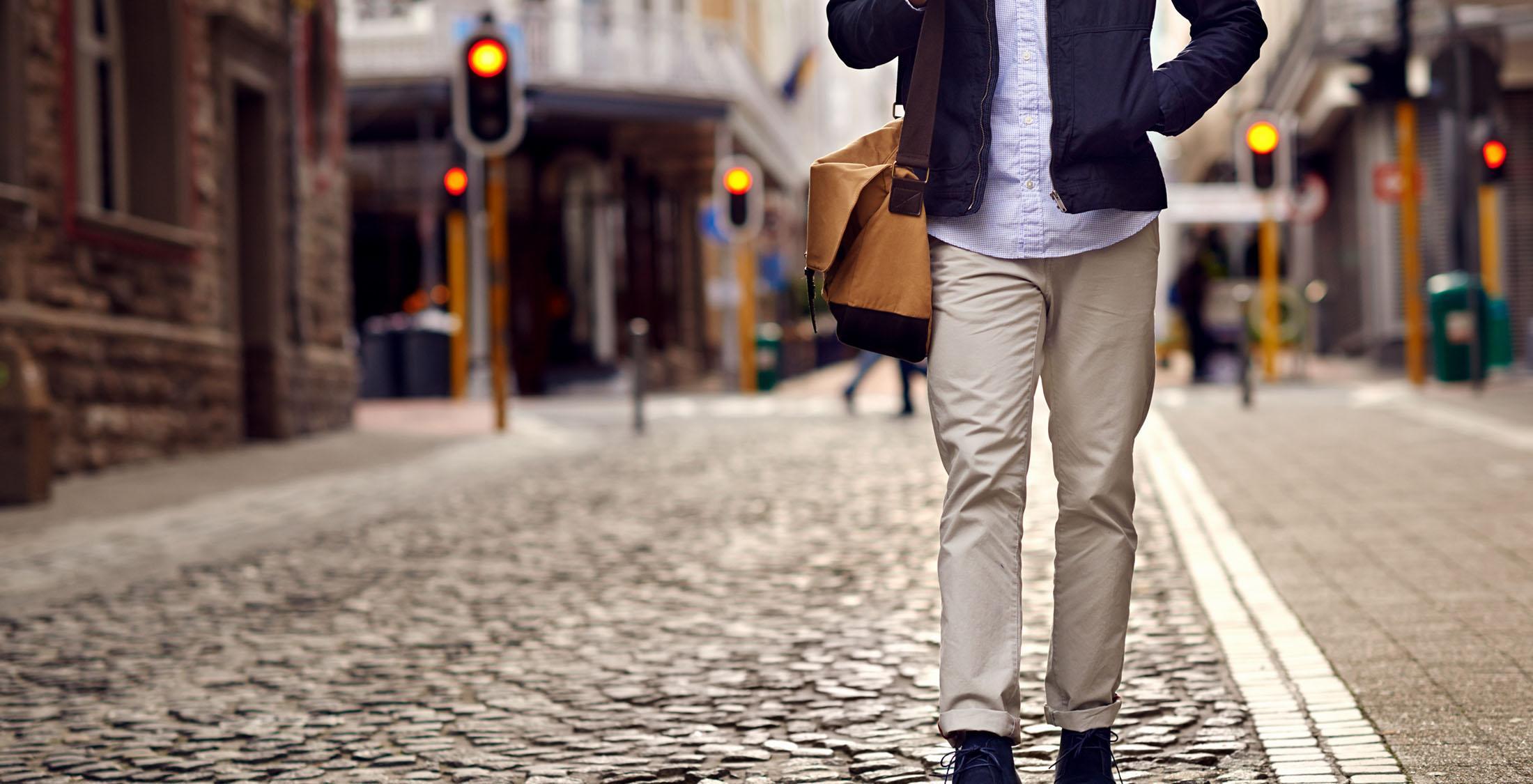 man walking down cobblestone street