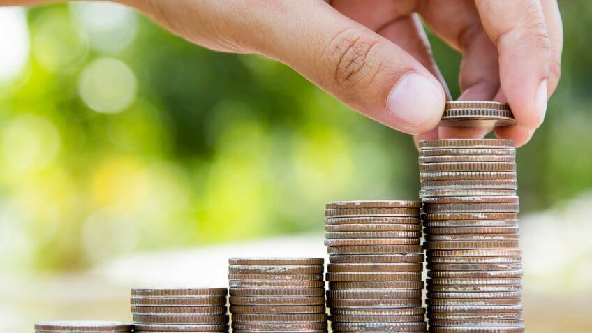 Saving and Business concept, hand putting coins to coin stack growing graph on green bokeh background.