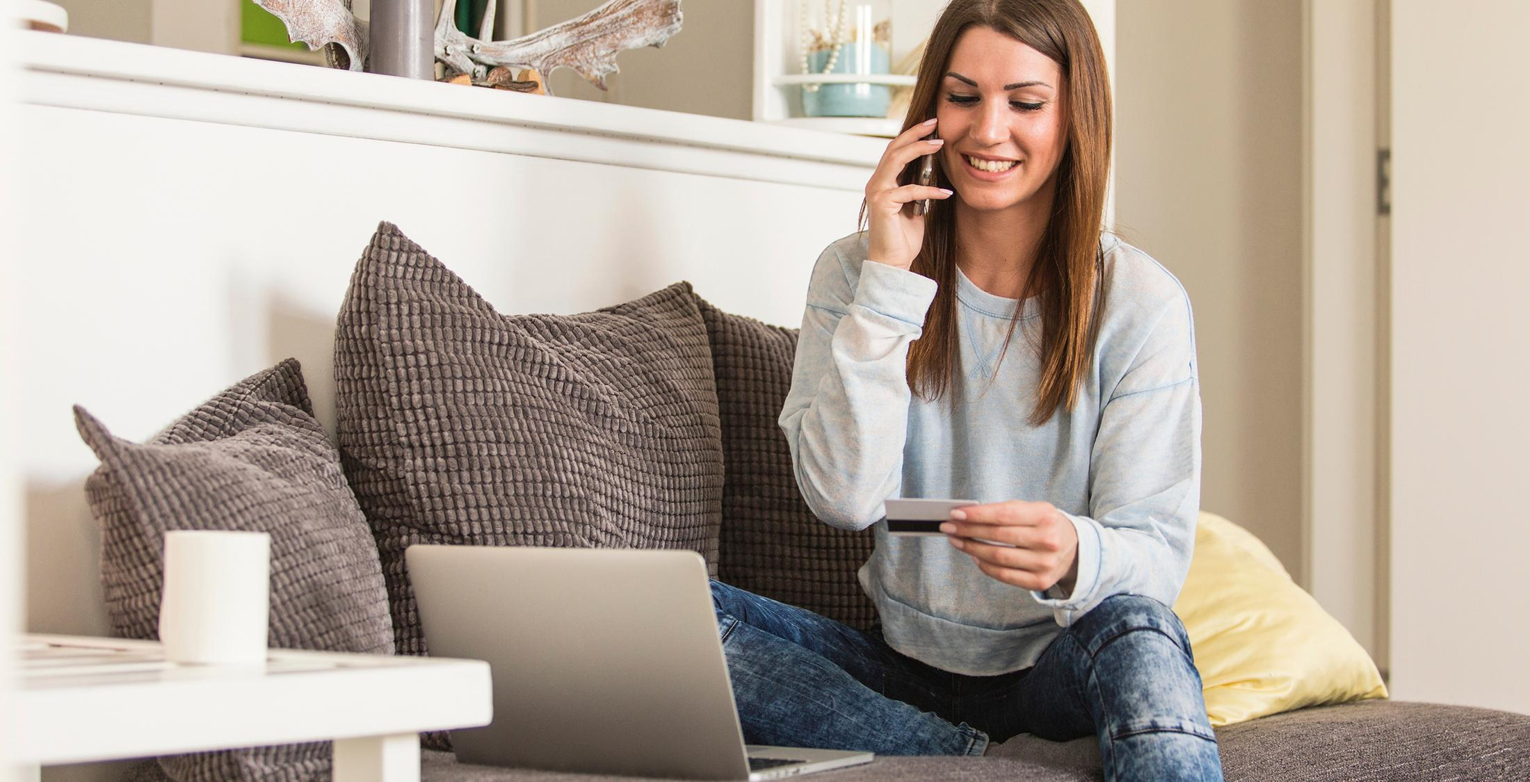 Young woman holding credit card and using laptop at home