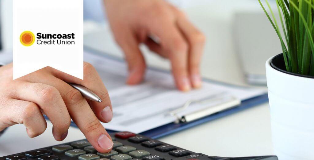 suncoast credit union hand typing on calculator