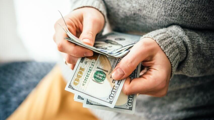 woman counting $100 bills cash money