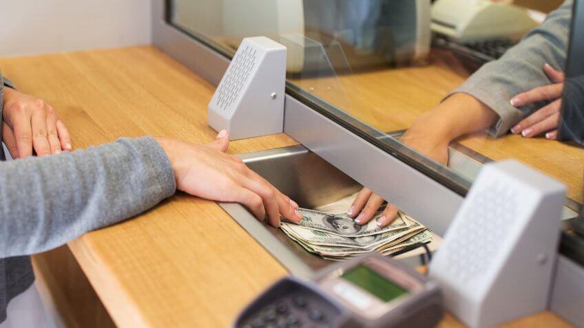11902, Horizontal, woman depositing USD money into bank
