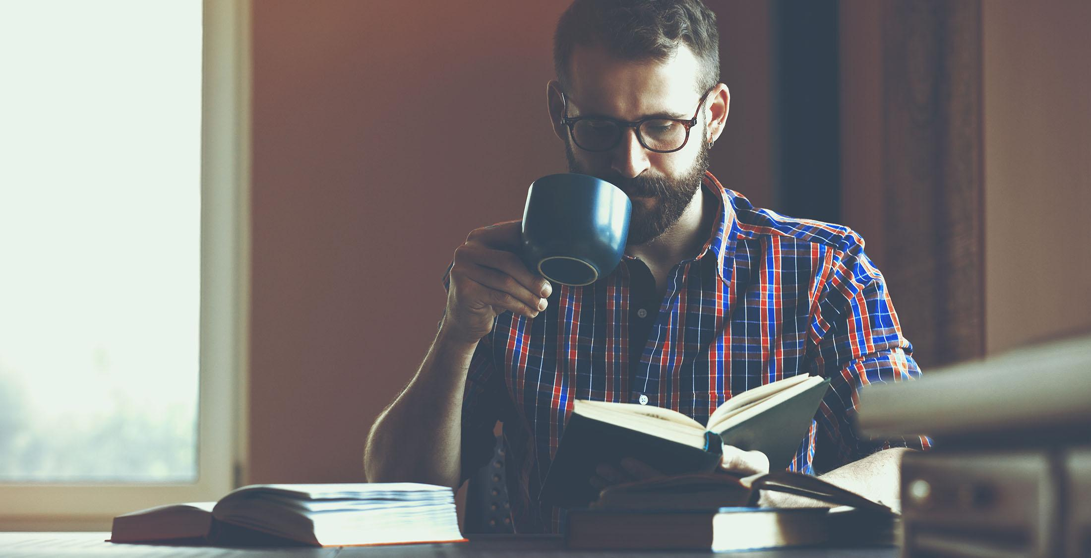 man sipping on coffee and reading a book