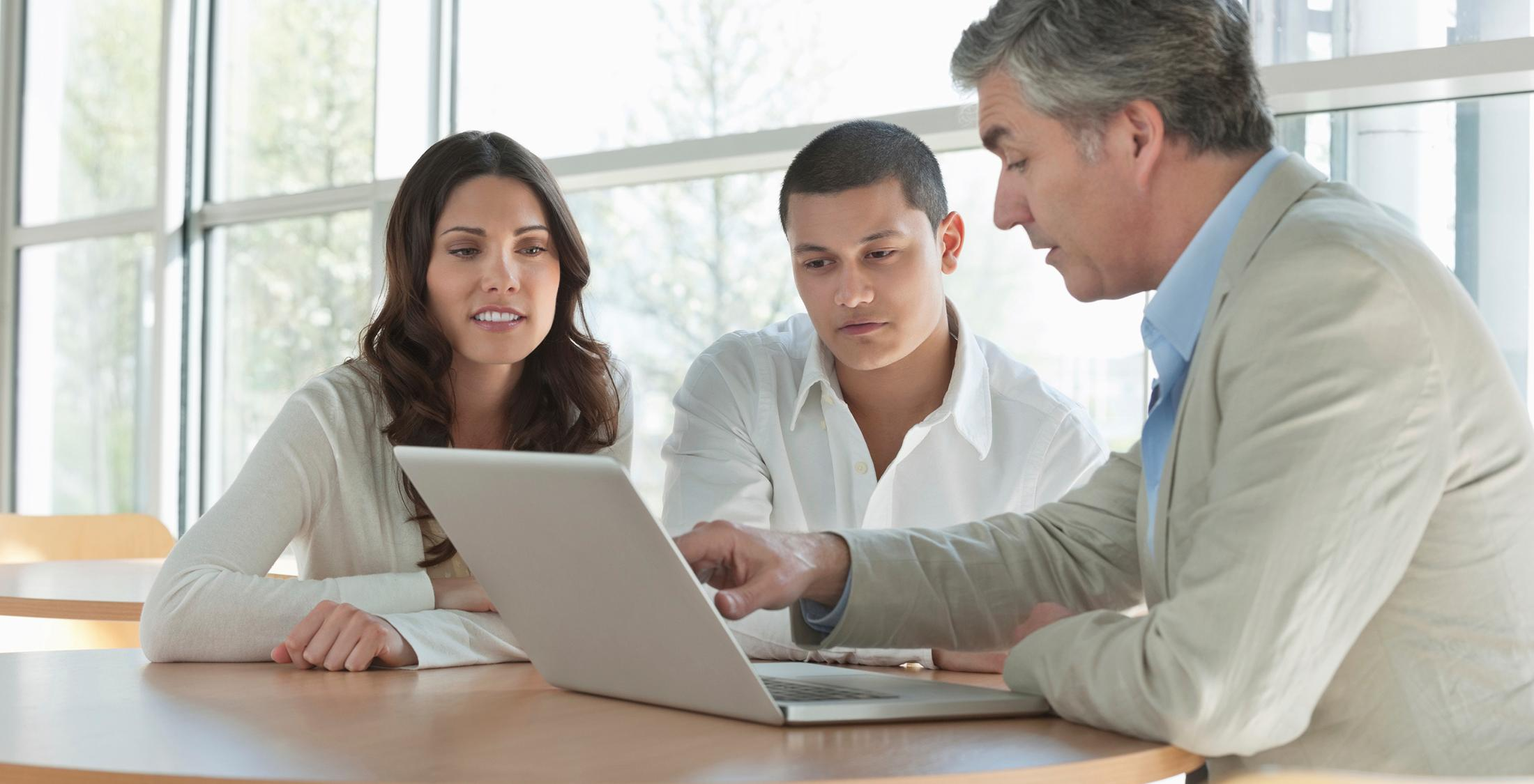 Mature financial advisor explaining an investment scheme on laptop to young couple