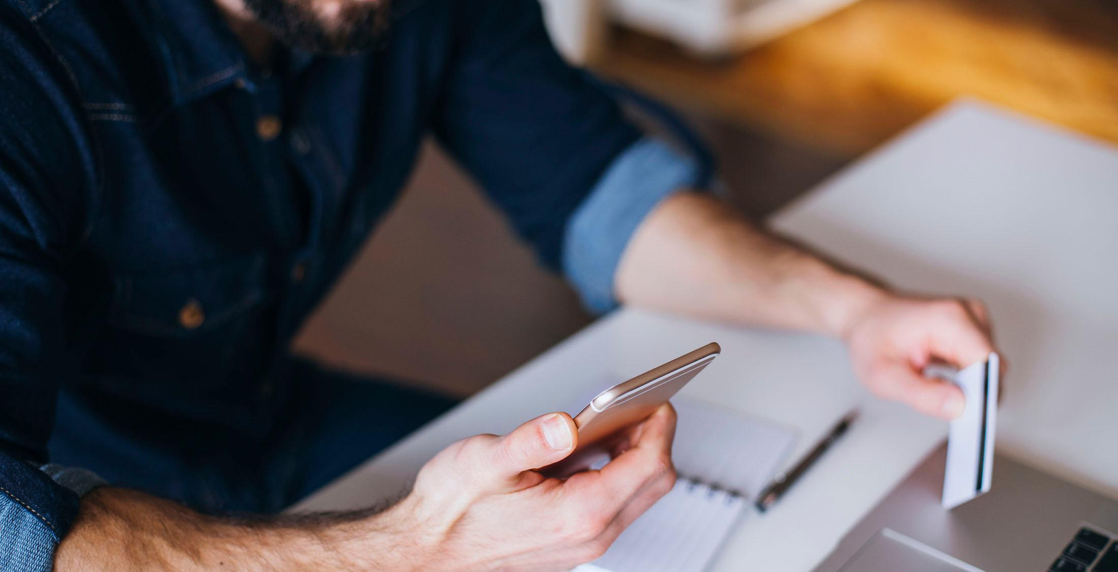 Man using mobile phone and credit card to shop online