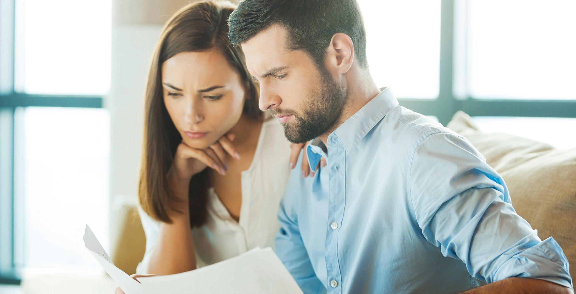 man holding documents and looking at them with woman