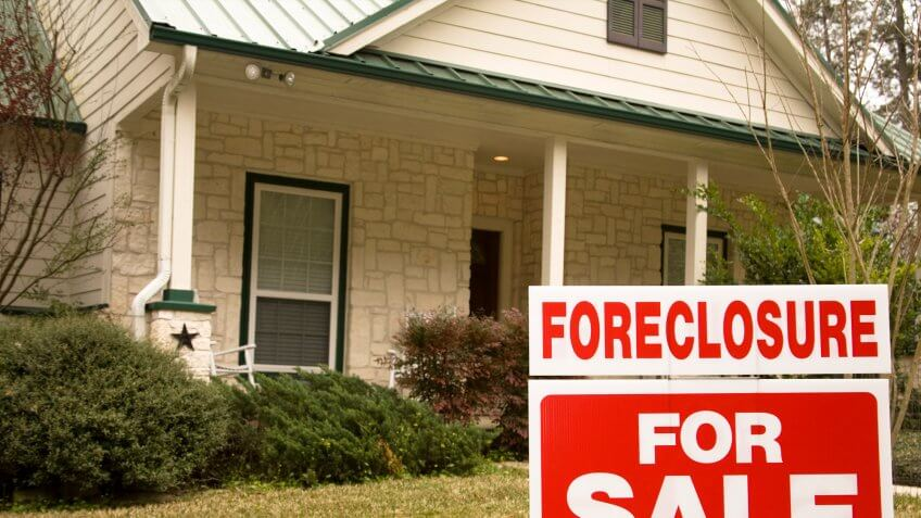 Foreclosure for sale sign on the lawn in front of a home