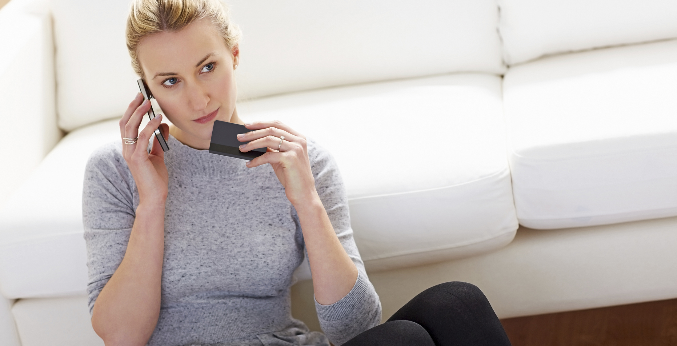 Thoughtful young woman on phone holding credit card at home