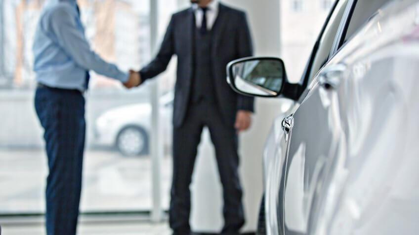 Handshake between two business people in a car showroom.