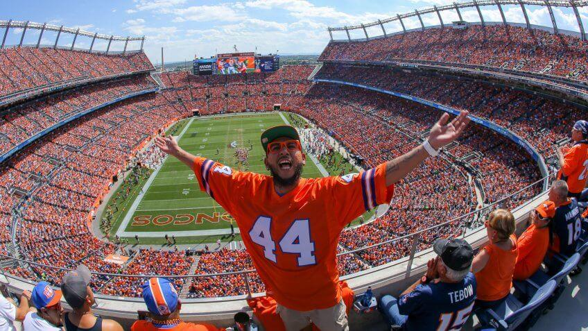 DENVER, CO - SEPTEMBER 14:  A Denver Broncos fan cheers in the upper level of the stadium during the first quarter of a game between the Denver Broncos and the Kansas City Chiefs at Sports Authority Field at Mile High on September 14, 2014 in Denver, Colorado.