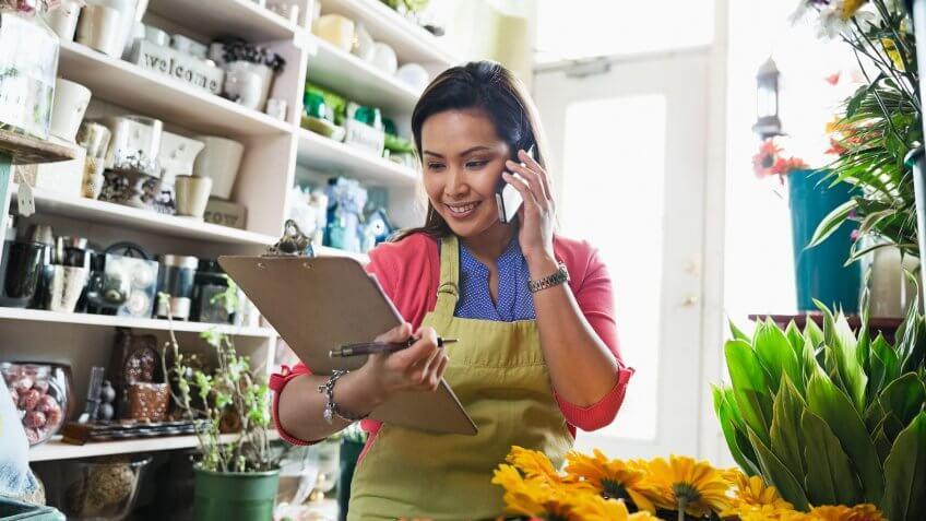 Female florist taking order on mobile phone in flower shop.