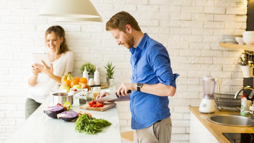Man cutting produce, making dinner.