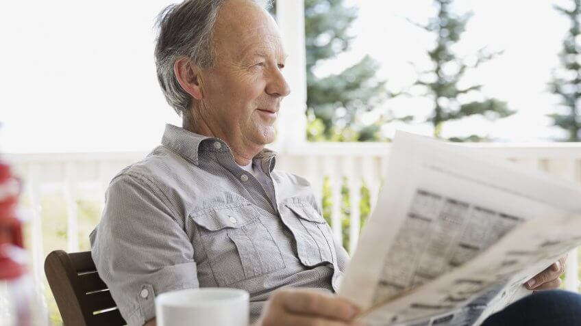 Senior man reading newspaper on porch.