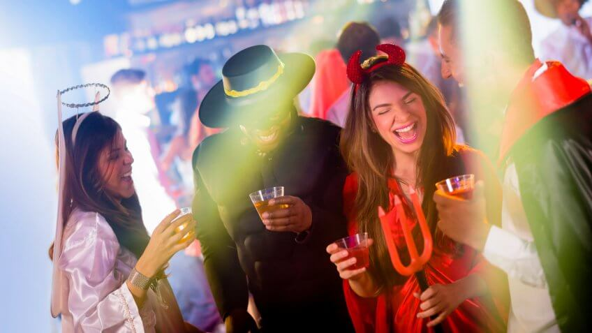 Group of people partying in Halloween and wearing different costumes at a nightclub.