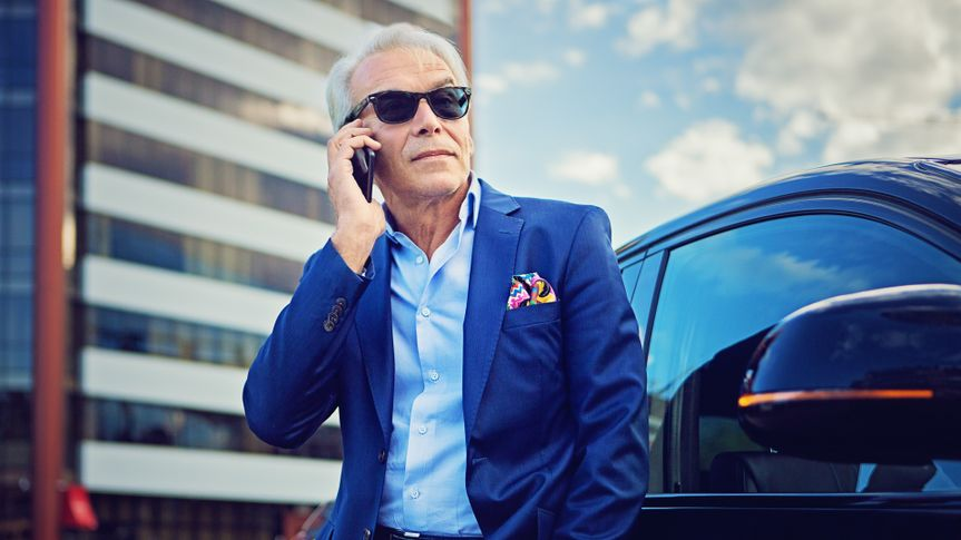 Businessman is talking using his mobile phone standing next to his car.