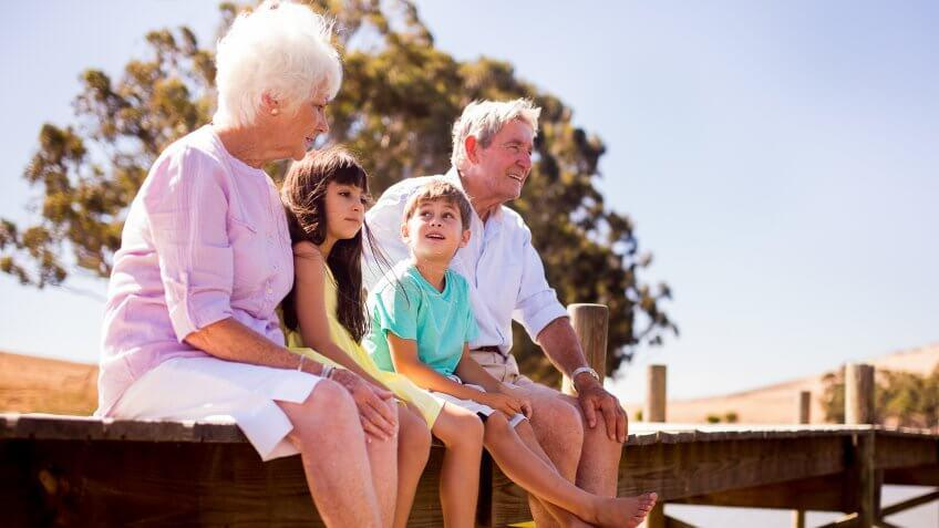 Retired grandparents sitting happily with their grandchildren on a jetty while on summer vacation.