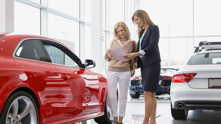 Saleswoman showing woman brochure in car dealership showroom.