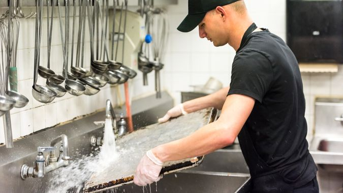 young dishwasher working at a restaurant kitchen.