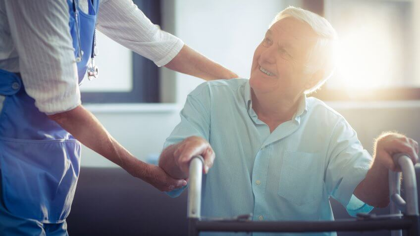 Female doctor helping senior man to walk with walker at home.