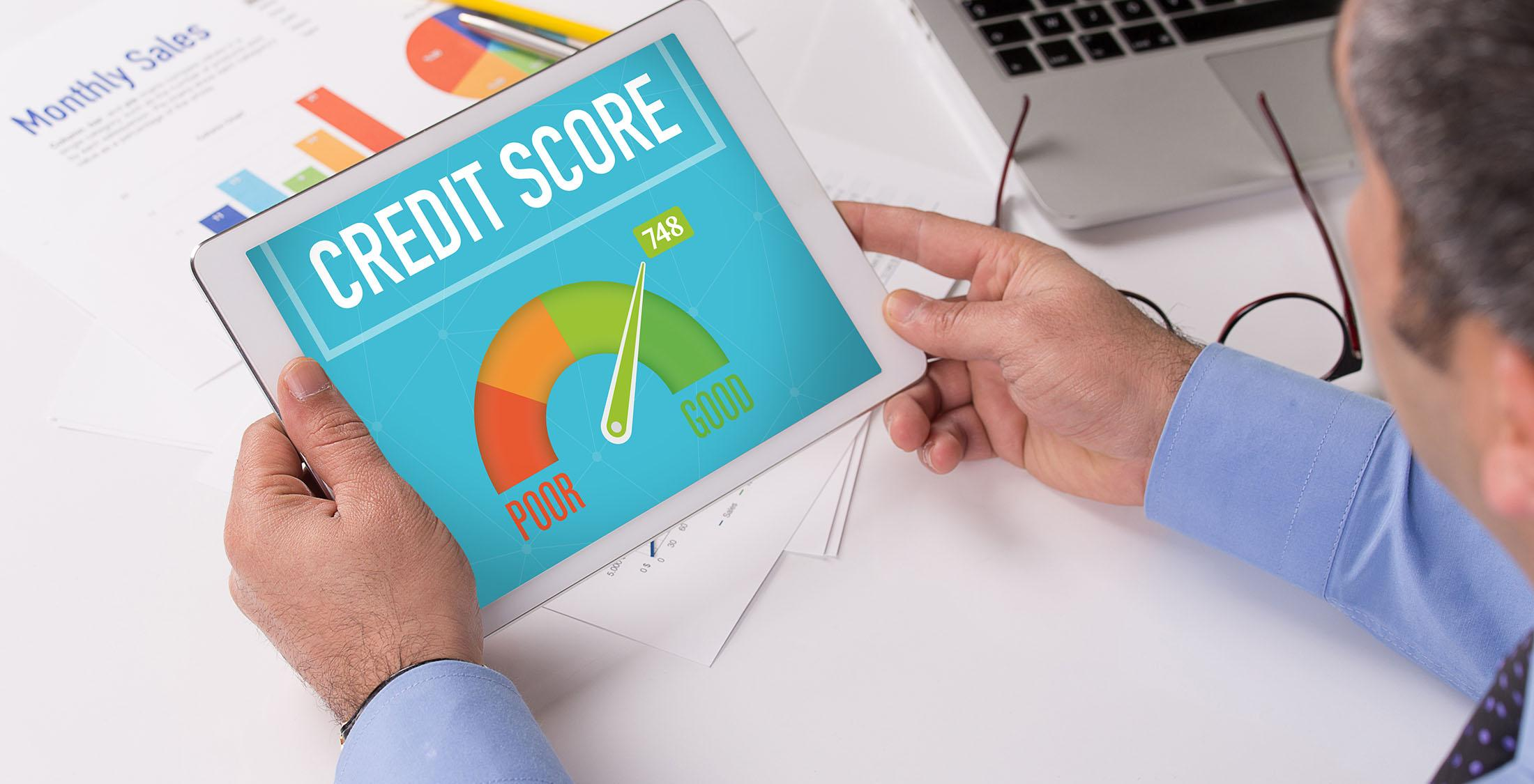 man looks at good credit score on tablet