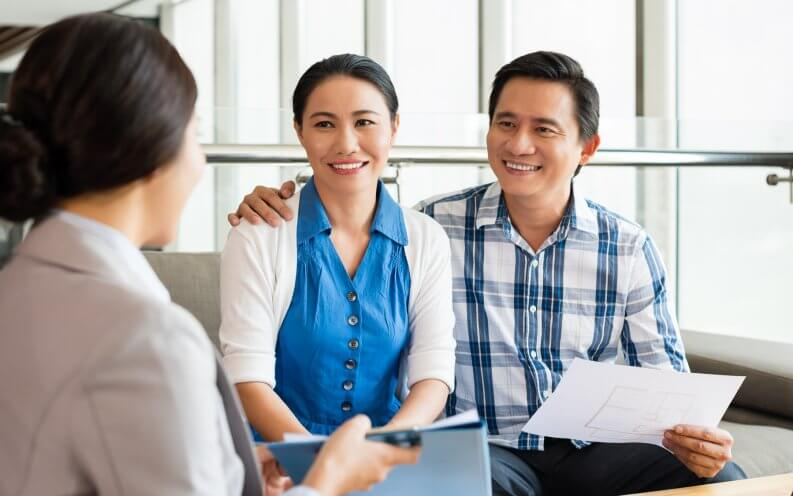asian couple meeting with advisor holding papers