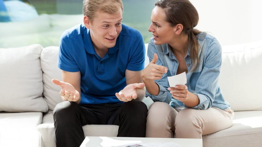 man and woman arguing looking at a piece of paper