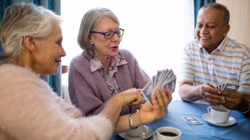 Smiling senior woman showing cards to friends while playing at table in nursing home.