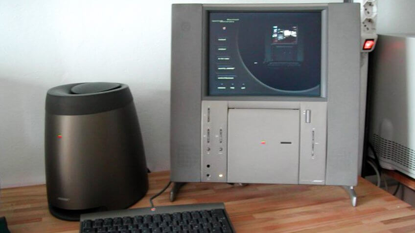 A Twentieth Anniversary Macintosh computer (right), a subwoofer (left), and a keyboard (front).
