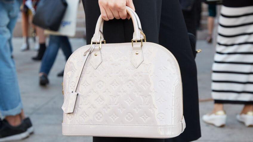 MILAN - SEPTEMBER 22: Woman with white Louis Vuitton bag before Cristiano Burani fashion show, Milan Fashion Week street style on September 22, 2016 in Milan.